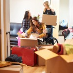 A group of three female university students move into their shared flat , and start to unpack boxes. One of the students is a wheelchair user and is chatting to her new friends as they unpack their boxes in a communal lounge .